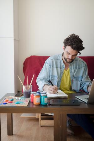 trabajando en casa: apuesto inconformista dise�ador hombre moderno de trabajo en casa usando la computadora port�til en casa Foto de archivo