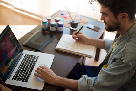 ハンサムな流行に敏感な現代人デザイナーの作業ホーム自宅のラップトップを使用して