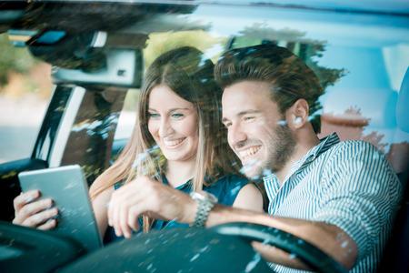 jovenes enamorados: hermosas j�venes amantes de la pareja que usa la tableta en el recorrido del coche
