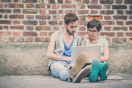 couple of friends young  man and woman using laptop in the city photo