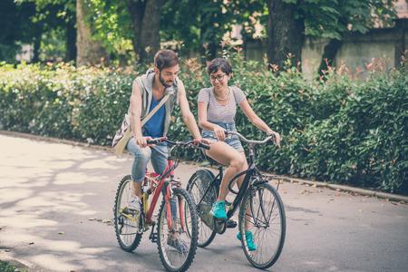 Coppia di amici giovane uomo e donna a cavallo della bici in città Archivio Fotografico - 32232132