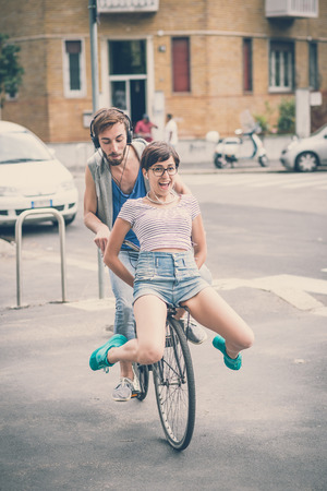 couple of friends young  man and woman riding bike in the city photo