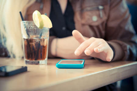close up of woman hands using smart phones at the bar  photo