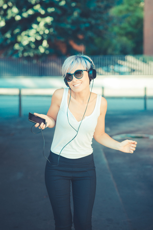 young beautiful short blue hair hipster woman with headphones music in the city photo
