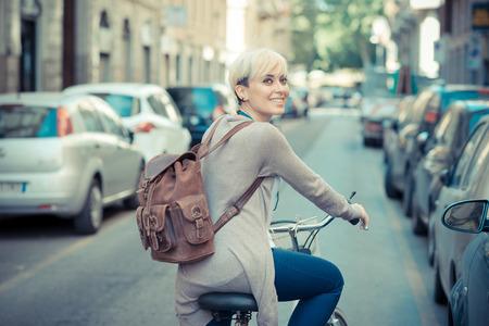 도시에서 아름 다운 젊은 금발의 짧은 머리 유행을 좇는 여자 witk 자전거