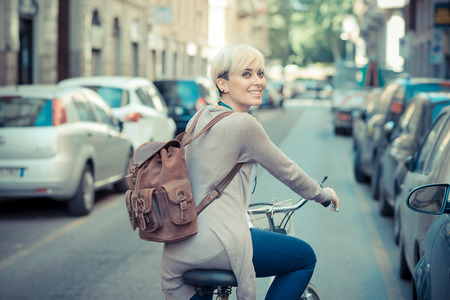 city bike: beautiful young blonde short hair hipster woman witk bike in the city