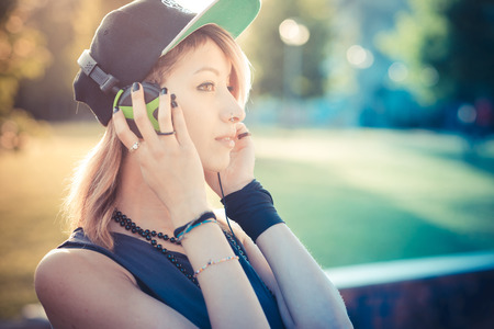 young beautiful model woman listening music in the city photo