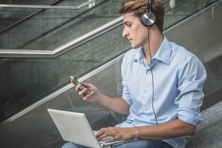 young model handsome blonde man with notebook smartphone and headphones in the city photo