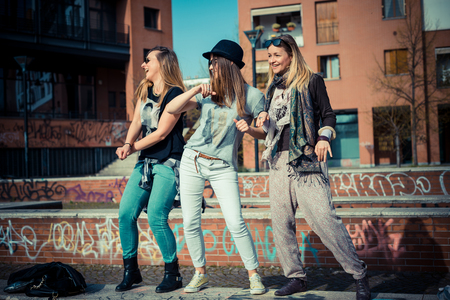 three beautiful friends authentic in urban contest dancing photo