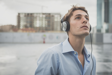 young model handsome blonde man with music headphones in the city photo