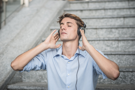 young model handsome blonde man with headphones in the city photo