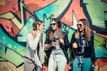 three beautiful friends authentic in urban contest listening to music photo
