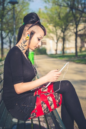 young beautiful punk dark girl using tablet in urban landscape photo