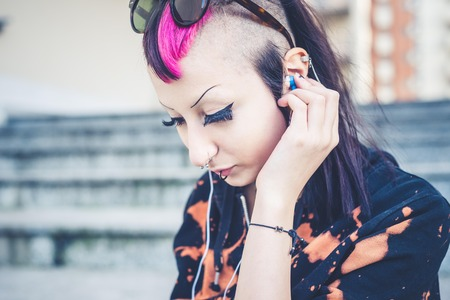 young beautiful punk dark girl listening music in urban landscape photo