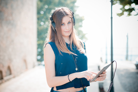 young beautiful hipster woman listening to music with headphones in the city photo