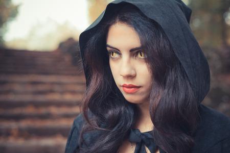 mooie donkere vampier vrouw met zwarte mantel en kap halloween