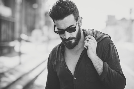 estilo urbano: joven apuesto hombre atractivo modelo con barba en contexto urbano