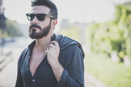都市文脈で若いハンサムな魅力的なひげを生やしたモデル男