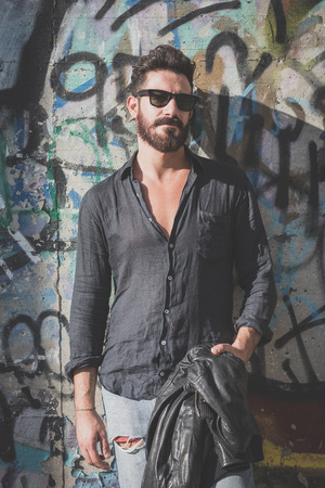appealing attractive: young handsome attractive bearded model man in urban context Editorial