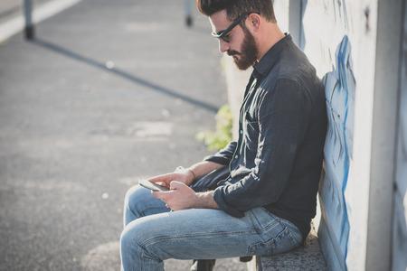 都市のコンテキストのスマート フォンを使用して若いハンサムな魅力的なひげを生やしたモデル男
