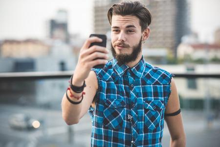 도시의 젊은 잘 생긴 수염이 유행을 좇는 사람 selfie 스톡 콘텐츠