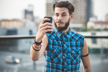 young handsome bearded hipster man selfie in the city Standard-Bild