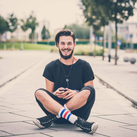 young handsome bearded hipster man using smartphone and listening music with earphones in the city Imagens