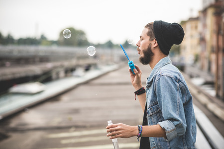 young handsome bearded hipster man blowing bubbles soap in the city photo
