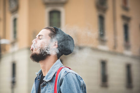 young handsome bearded hipster man smoking cigarette in the city photo