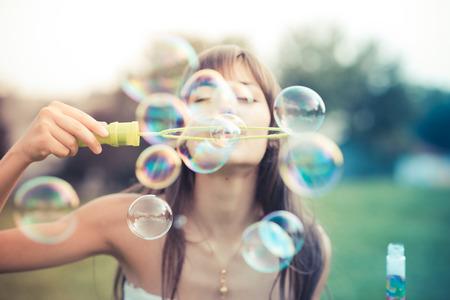 schöne junge Frau mit weißem Kleid weht Blase in der Stadt
