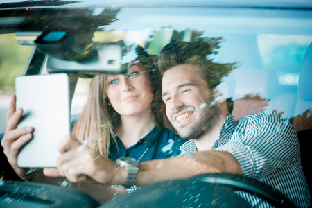 young beautiful couple lovers using tablet in the car travel photo
