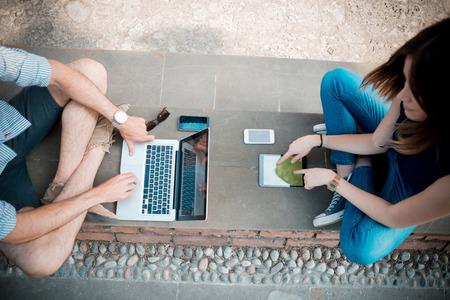 jong koppel met behulp van technologie multitasking smarpthone tablet en laptop in de straat