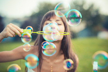 krásná mladá žena s bílými šaty vyfukování bublin
