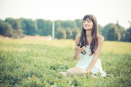 escuchando musica: hermosa mujer joven con vestido blanco de música escucha en el parque Foto de archivo