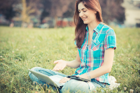 beautiful young hipster woman using laptop and tablet in the park photo