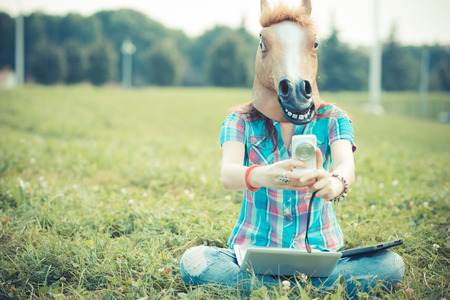 horse mask unreal hipster woman using technology in the park