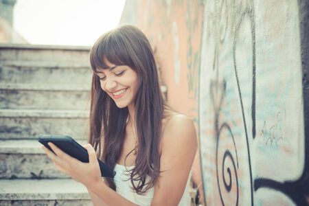 attractive young woman: beautiful young woman with white dress using tablet in the city Stock Photo
