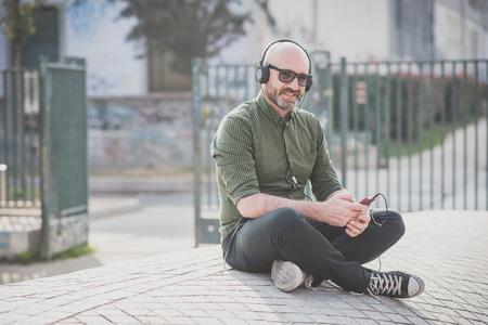 ハンサムな中年男は、市内で音楽を聴く 写真素材