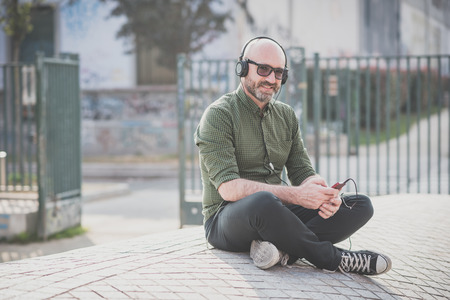 handsome middle aged man listening music in the city Фото со стока