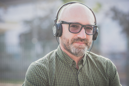 grizzled: handsome middle aged man listening music in the city Stock Photo