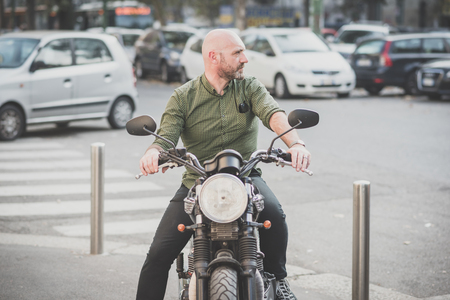 grizzled: handsome middle aged man motorcyclist in the city Stock Photo