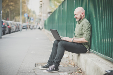 bald men: handsome middle aged man using notebook in the city