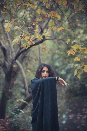 beautiful dark vampire woman with black mantle and hood halloween photo