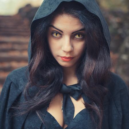 블랙 맨 틀과 후드와 함께 아름 다운 어두운 뱀파이어 여자 할로윈