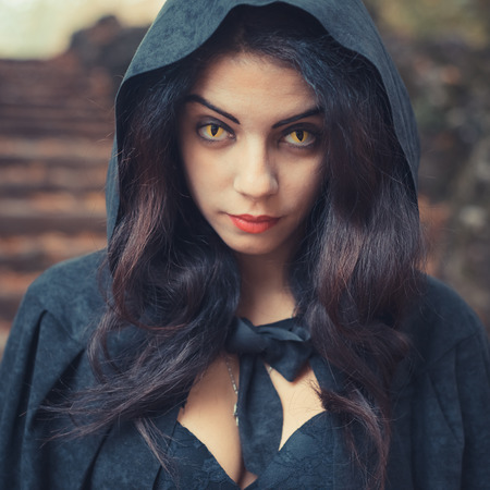 beautiful dark vampire woman with black mantle and hood halloween Stock Photo - 34000440