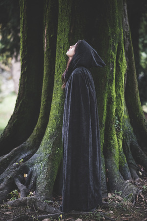 beautiful dark vampire woman with black mantle and hood halloween photo