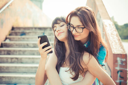 beautiful hipster young women sisters friends using smartphone  in the city photo