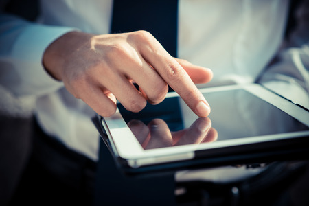 close up businessman man hand using tablet device outdoor Stock Photo