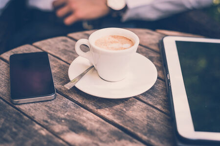 cup of coffe tablet and smart phone on wooden table photo