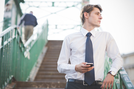 young handsome elegant blonde model man using smartphone in the city photo